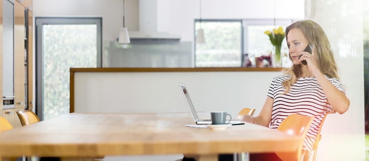 Frau sitzt vor Laptop am Telefon